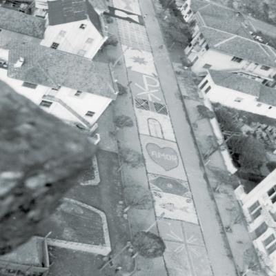 A tradição dos tapetes coloridos de Corpus Christi é marca registrada de Flores da Cunha. Neste ano, devido à pandemia da Covid-19 não será possível confeccionar as obras. Na década de 1960, os tapetes de serragem contornavam as principais quadras do Centro. Na foto, do alto do campanário, vê-se, além dos tapetes, os alicerces da construção do salão paroquial.