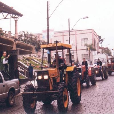 A foto é de 1999, das comemorações do Colono e Motorista da época. A Associação dos Motoristas e o Sindicato Rural promoviam, em conjunto, a Festa de Integração Colono e Motorista, com celebração na Igreja Matriz e benção dos veículos e tratores agrícolas.