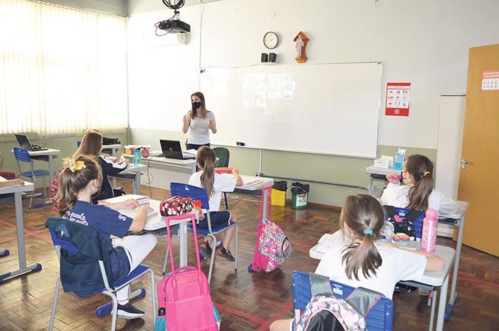 Enquanto alguns alunos voltam às salas, outros aparecem virtualmente no quadro branco.