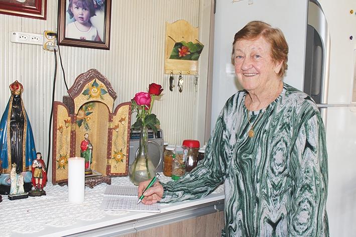 Aos 84 anos, Olga Gelain contabiliza mais de 80 nomes em seu caderno de orações a São Paulo.