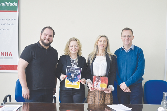 A escritora Andréia Belusso, junto com o diretor de Cultura, Michael Molon, a secretária de Educação, Ana Paula Weber, e o prefeito Lídio Scortegagna.